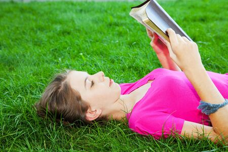 Teen girl reading the Bible outdoors lying on the grass photo