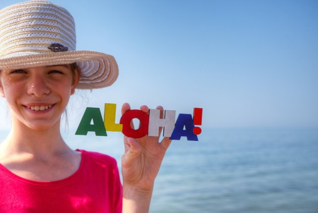 Teen girl at a beach holding word 'Aloha' photo