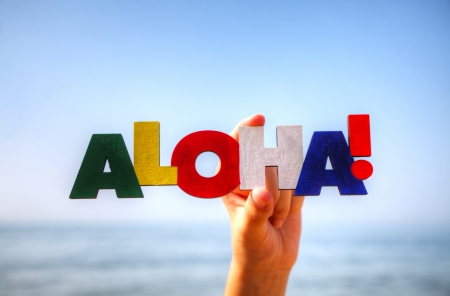 Female's hand holding colorful word 'Aloha' against blue background photo