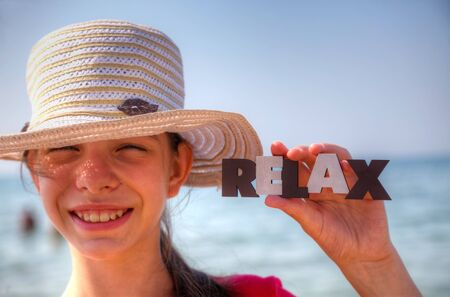 single word: Teen girl at a beach holding word Relax