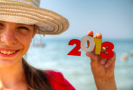 Teen girl at a beach holding wooden number 2013 photo
