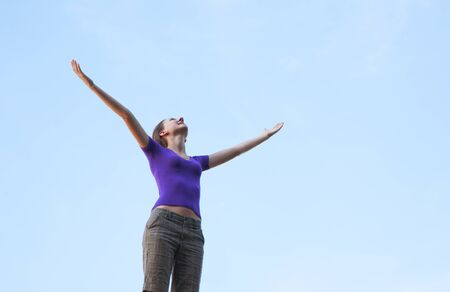 Young woman staying with raised hands against blue sky photo