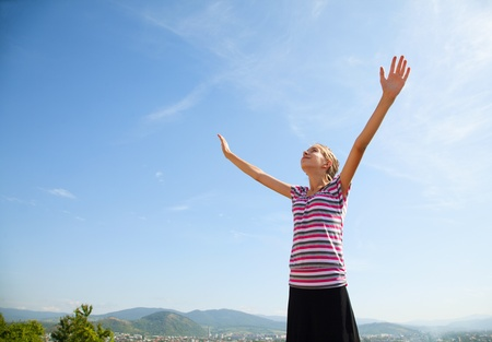 Teenage girl staying with raised hands against blue sky photo