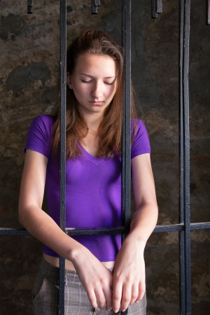 Young woman looking from behind the bars photo
