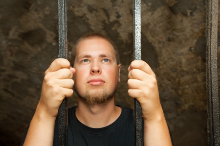 Young man looking from behind the bars