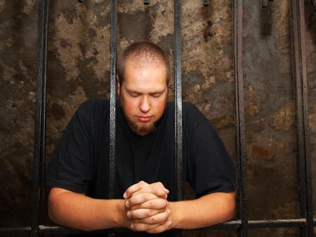 cellule prison: Jeune homme priant rester derrière les barreaux