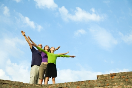 Three young people staying with raised hands against blue sky