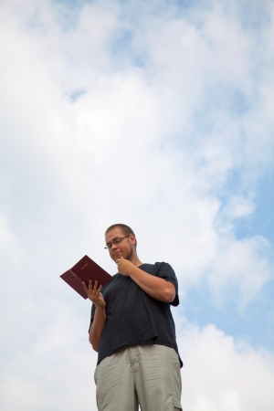 Young man staying with the Bible against blue sky Stock Photo - 14656023