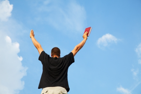 raised: Young man staying with raised hands against blue sky Stock Photo