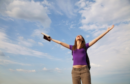 Young woman staying with raised hands against blue sky Stock Photo - 14656040