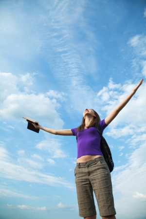 Young woman staying with raised hands against blue sky