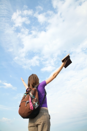 staying: Teenage girl staying with raised hands against blue sky Stock Photo