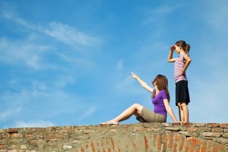 manos levantadas al cielo: Dos chicas adolescentes al aire libre mirando a lo lejos