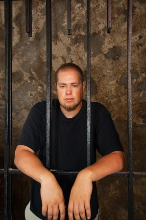Young man looking from behind the bars photo