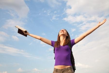 manos levantadas al cielo: Mujer joven qued�ndose con las manos en alto contra el cielo azul