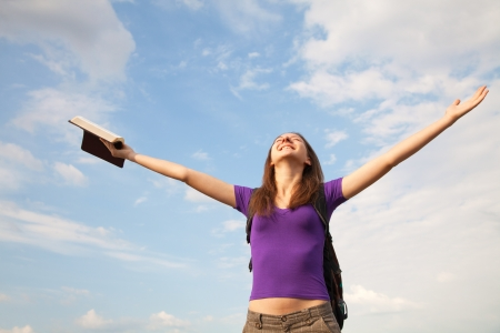emotional freedom: Young woman staying with raised hands against blue sky