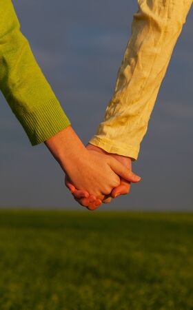 girls holding hands: Teen girls holding hands against blue sky