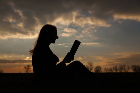 Teen girl reading book outdoors at sunset time photo