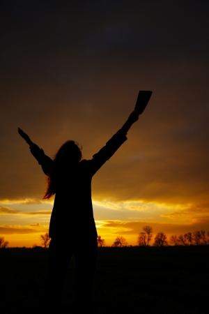 manos levantadas al cielo: Mujer quedarse con las manos levantadas en el momento de la puesta del sol