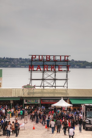 pike place market sign: SEATTLE - MAY 20, 2012: Famous Pike Place Public Market in Seattle, Washington with tourists. The Market opened August 17, 1907, and is one of the oldest continually operated public farmers markets in the US.
