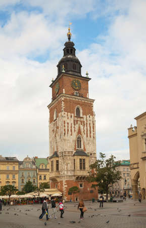 KRAKOW, POLAND - OCTOBER 11: Town hall tower at old market square with tourists on October 11, 2012 in Krakow. The square is a principal urban space located at the center of the city and – at roughly 40,000 sq. m – it is the largest medieval town squa Stock Photo - 17615202