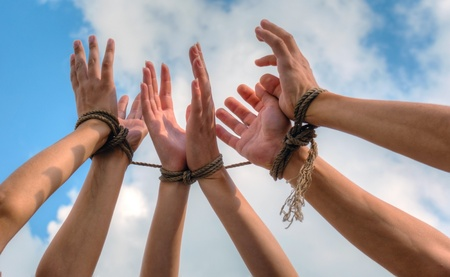 Three pairs of human hands tied up together with rope photo