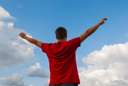Young man staying with raised hands against blue sky Stock Photo - 17669646