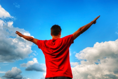 Young man staying with raised hands against blue sky Stock Photo - 17669649