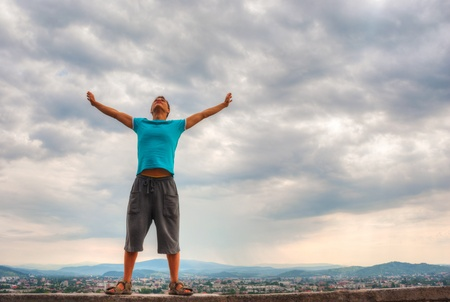 Young man staying with raised hands against blue sky Stock Photo - 17669647