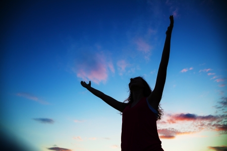 Woman staying with raised hands at the sunset time Stock Photo - 17817339