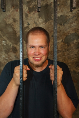 Young man looking from behind the bars Stock Photo - 17817326