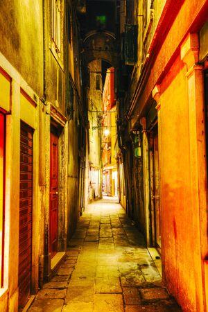 Narrow street in Venice, Italy at night time photo