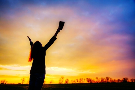 orando: Mujer quedarse con las manos levantadas en el momento de la puesta del sol