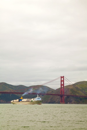 Ocean vessel under Golden Gates bridge in San Francisco in the morning photo