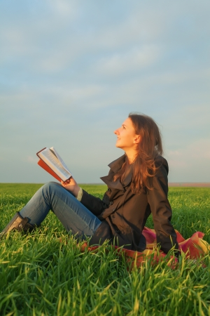 bible reading: Teen girl reading the Bible sitting outdoors at sunset time Stock Photo