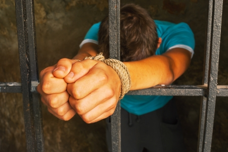 Man behind the bars with hands tied up with rope  photo