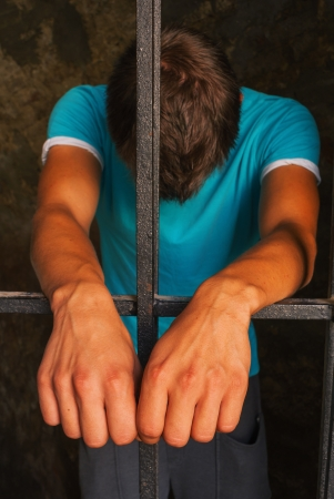 Man staying behind the bars photo