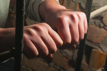an inmate: Hands behind the bars against the brick wall Stock Photo