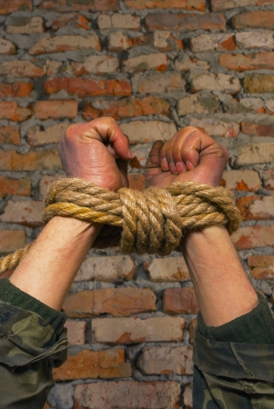 human trafficking: Hands tied up with rope against brick wall Stock Photo