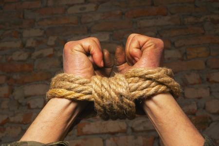 derechos humanos: Hands atados para arriba con cuerda en contra de ladrillo pared