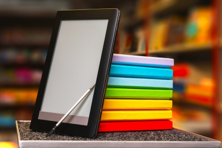 Stack of colorful books with electronic book reader at a book store Stock Photo