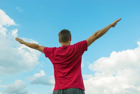 Young man staying with raised hands against blue sky Stock Photo - 18820723