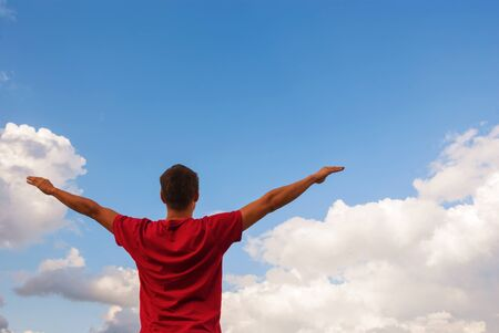 Young man staying with raised hands against blue sky Stock Photo - 18822921