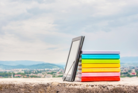 Stack of colorful books with electronic book reader against blue sky photo