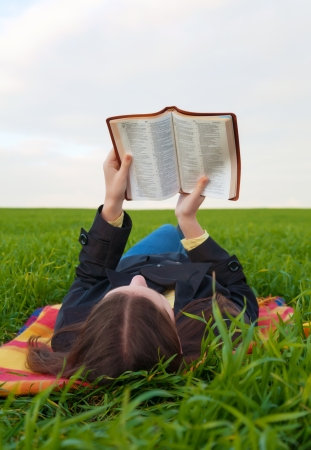 Teen girl reading the Bible outdoors at sunset time