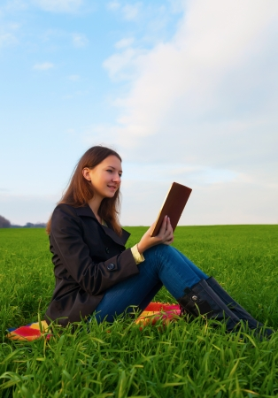 Teen girl reading the Bible sitting outdoors at sunset time photo