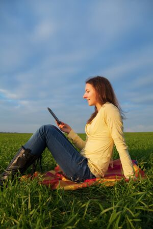 Teen girl reading electronic book sitting outdoors photo