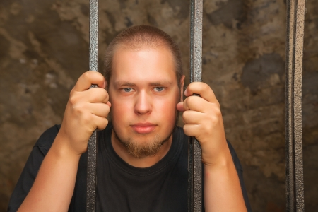 Young man looking from behind the bars Stock Photo - 18822957