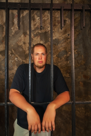 inmate: Young man looking from behind the bars
