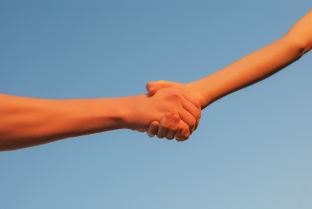 Hands shaking each other against blue sky Stock Photo - 20161453